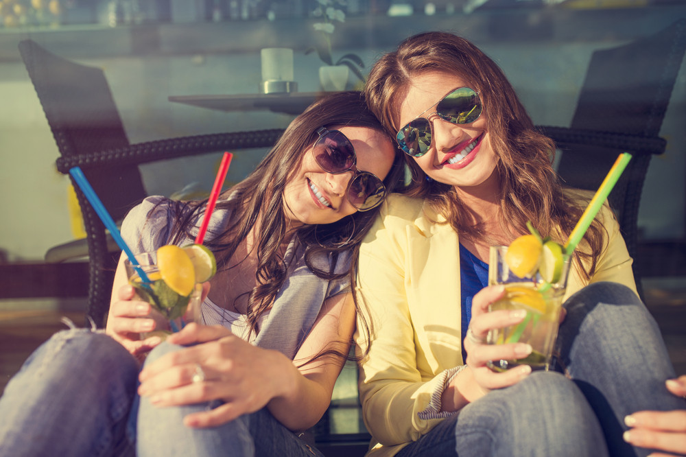 Beautiful young women with drinks having fun