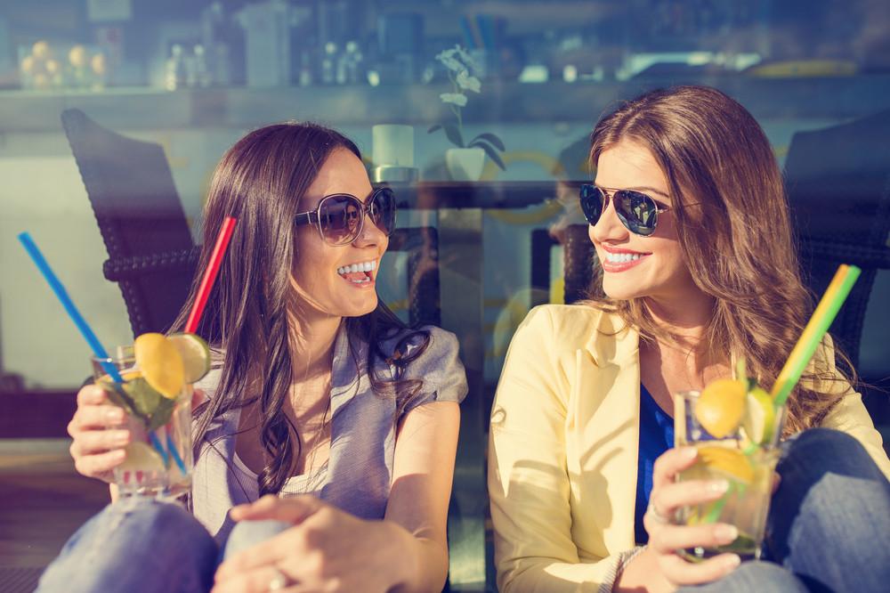 Beautiful young women with drinks having fun