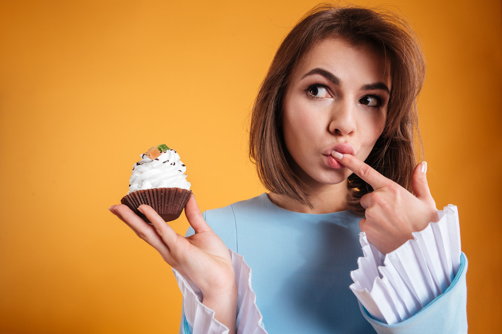 Beautiful ypensive young woman eating cake and thinking over yellow background