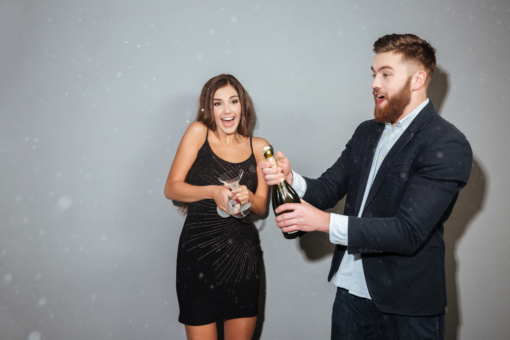 Beauty friends with champagne. open champage. gray background