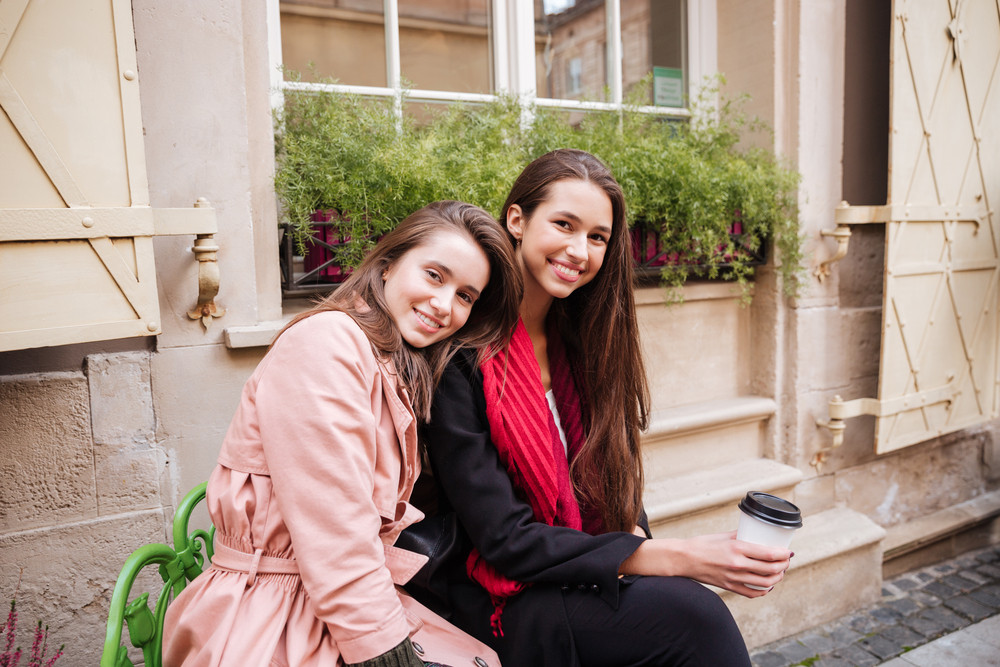 Beauty girls in coats are sitting on the street