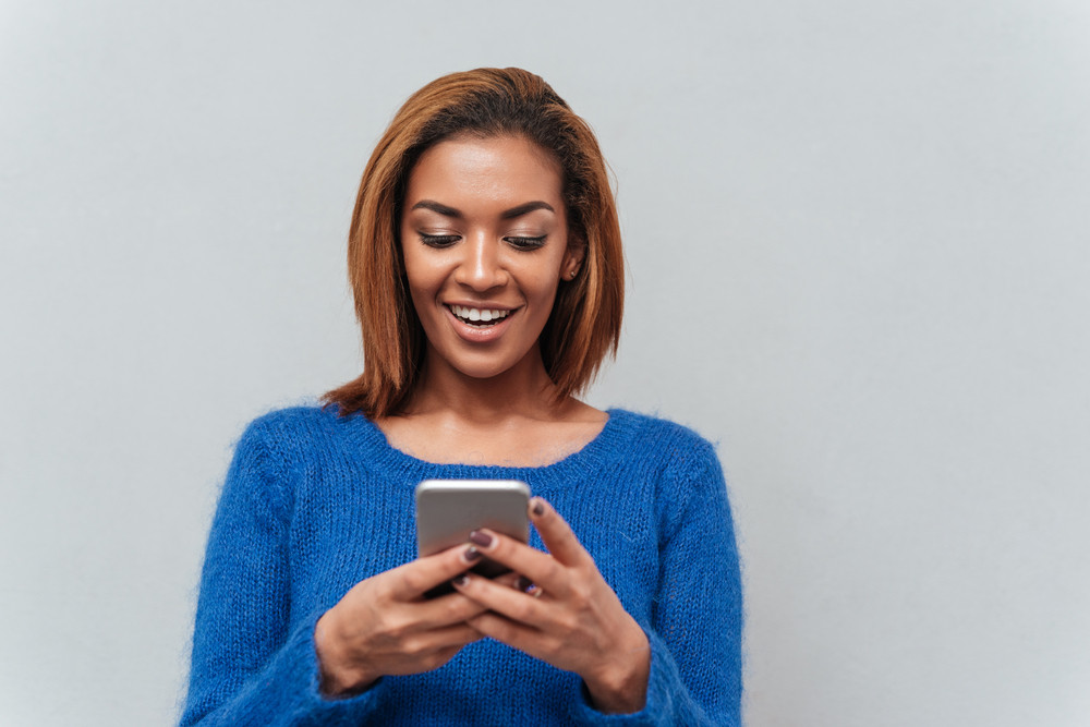 Beauty happy african woman in sweater looking at phone and writing message. Isolated gray background