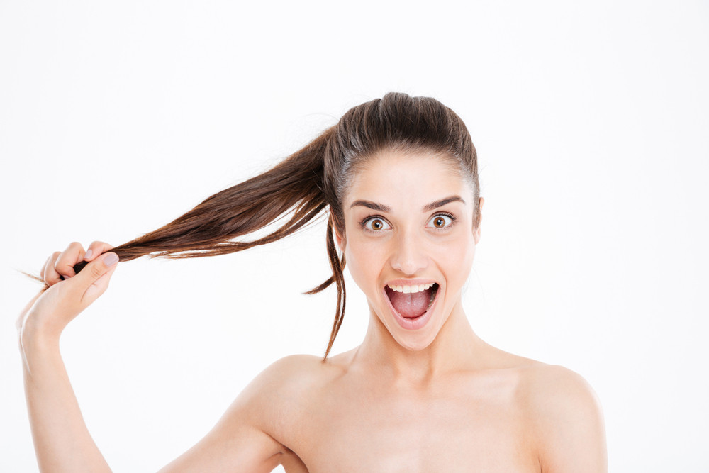 Beauty portrait of happy excited young woman touching her hair over white background