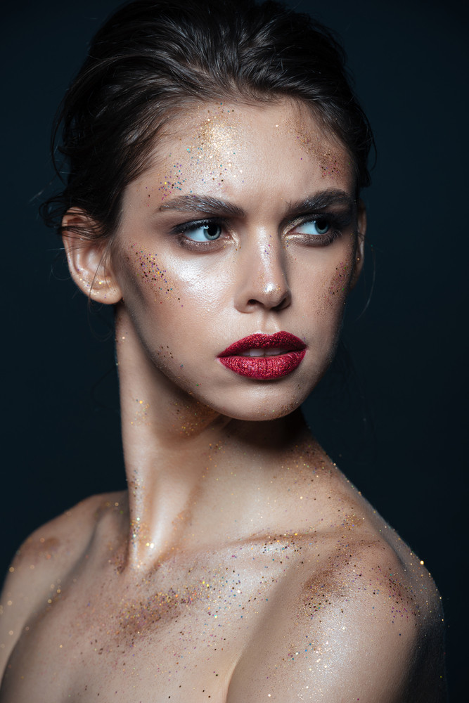 Beauty portrait of pretty young woman with sparkling makeup over black background