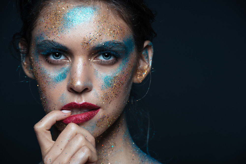 Beauty portrait of sensual young woman with bright shining makeup over black background
