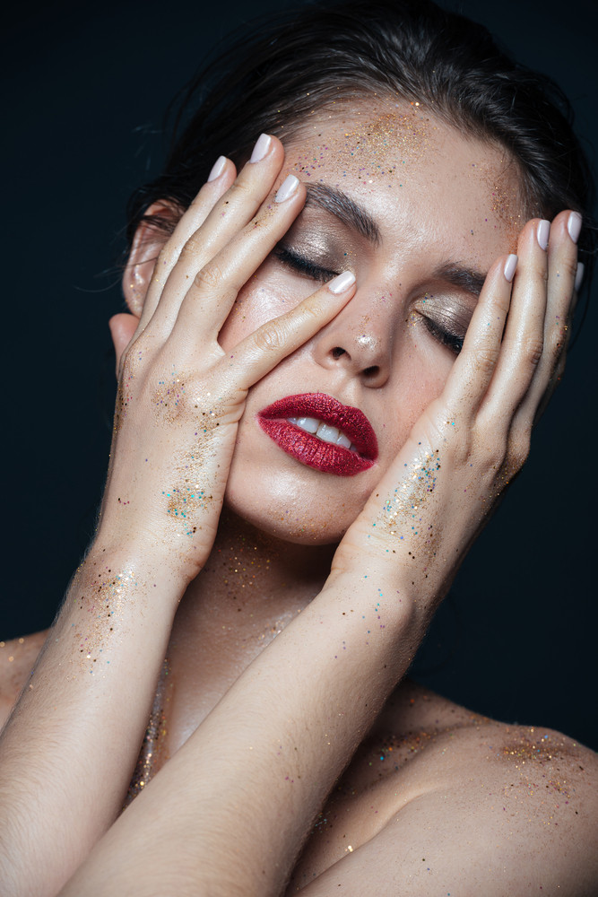 Beauty portrait of tender young woman with glitter makeup touching her face with both hands over black background