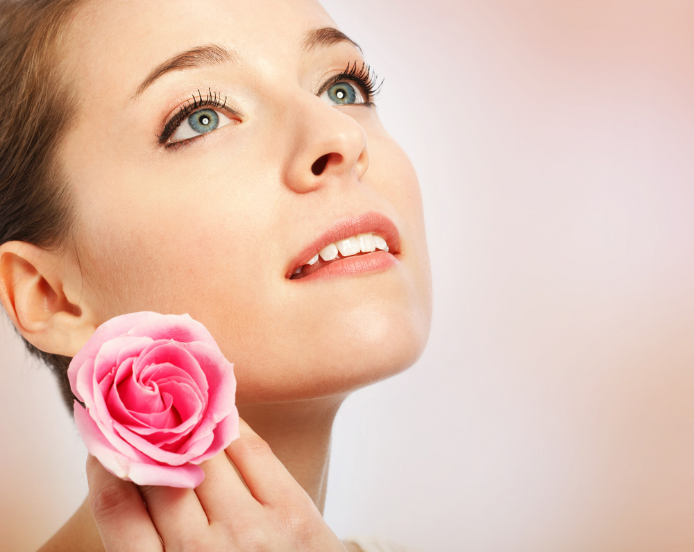 Beauty shot of a young woman with blue eyes close up holding a rose