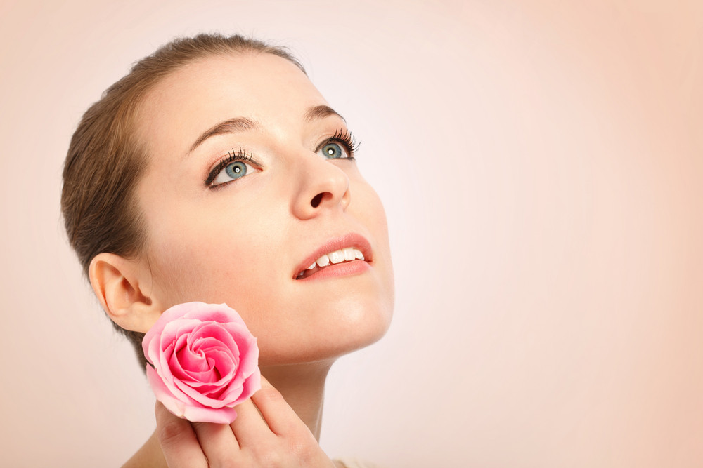 Beauty shot of a young woman with blue eyes  holding a rose
