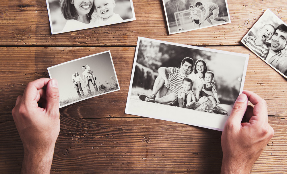 Black and white family photos laid on a table. Studio shot on wooden background.