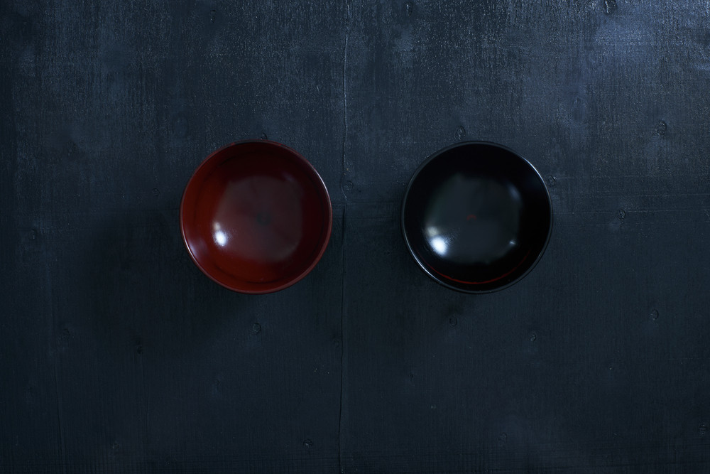 Black color wooden table top view. On the table are the Japanese wooden bowl.