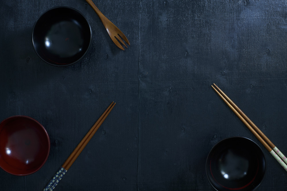Black color wooden table top view. On the table are the Japanese wooden spoon, chopsticks, bowl .