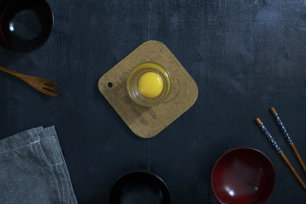 Black color wooden table top view. On the table are the Japanese wooden spoon, chopsticks, bowl,fresh raw eggs and table linen.