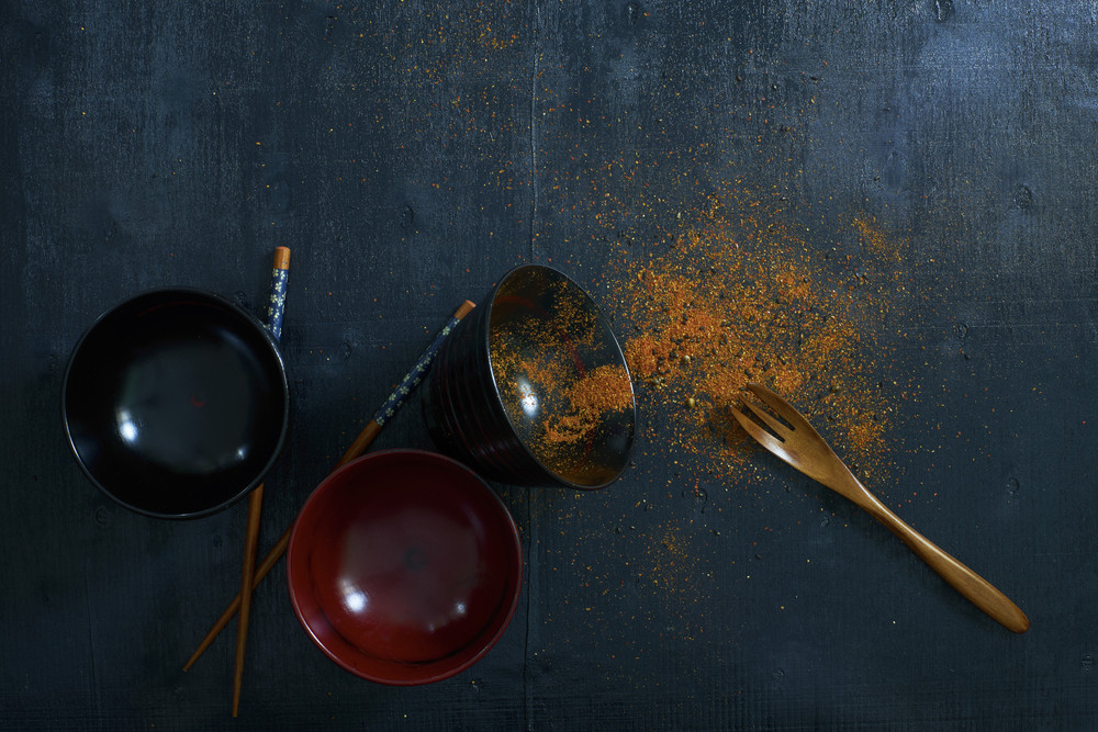 Black color wooden table top view. On the table are the Japanese wooden spoon,chopsticks,bowl and chili powder.