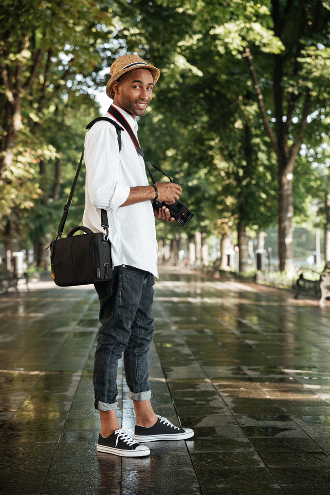 Black man in park. with hat and camera