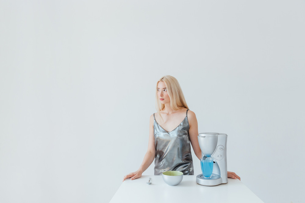 Blonde fashion glamour girl in silver shiny dress standing at the table isolated on the grey background