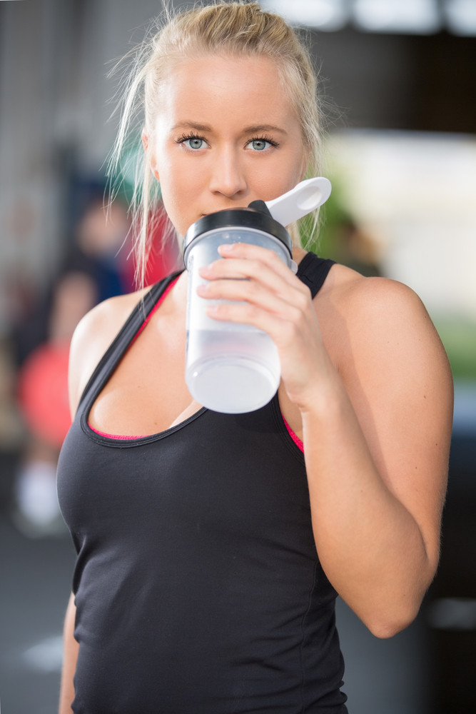 Blonde girl drinks water at fitness gym center