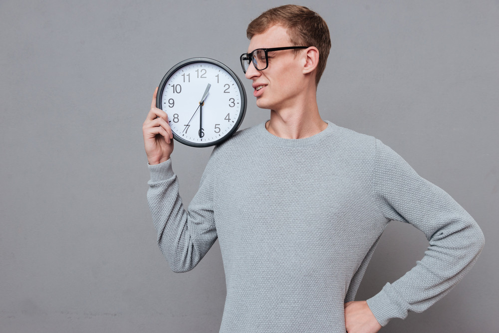 Botanist in glasses with clock. holding clock on shoulder. isolated gray background