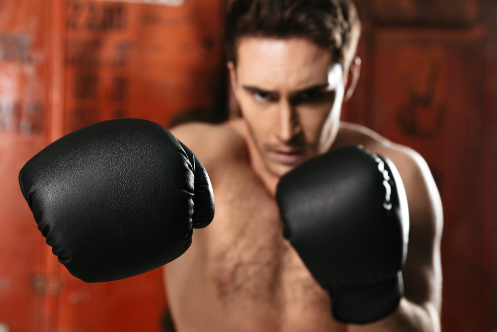 Boxer standing in a gym and posing with hands. Looking at camera. Focus on hands.
