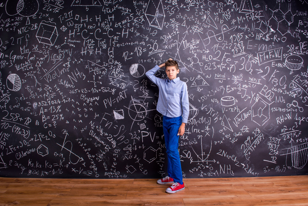 Boy in blue t-shirt, scratching head, against big blackboard with mathematical symbols and formulas