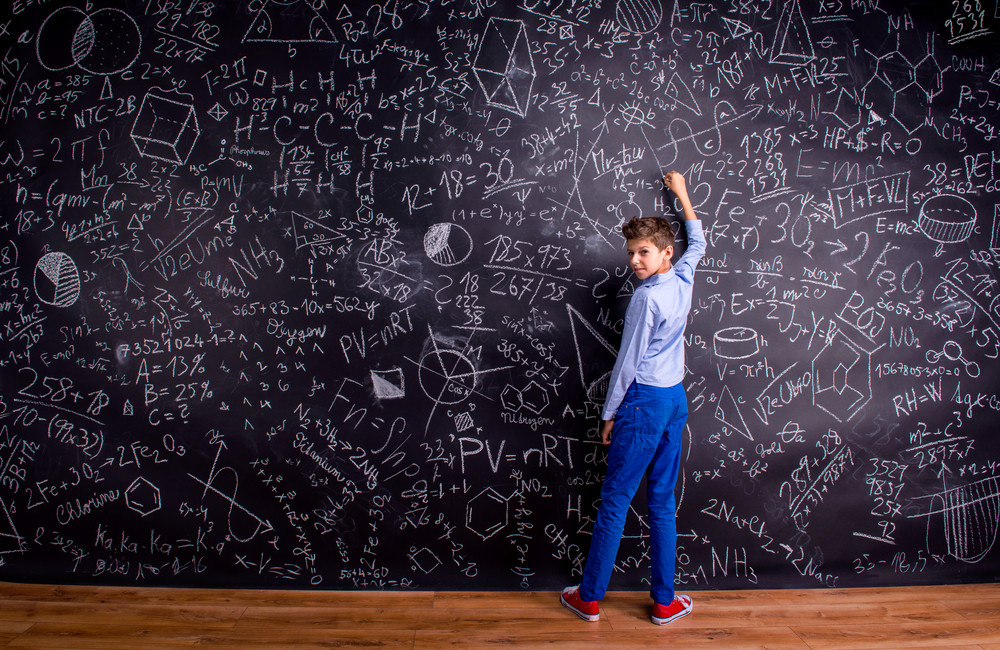 Boy in blue t-shirt writing with chalk on big blackboard with mathematical symbols and formulas, rear view