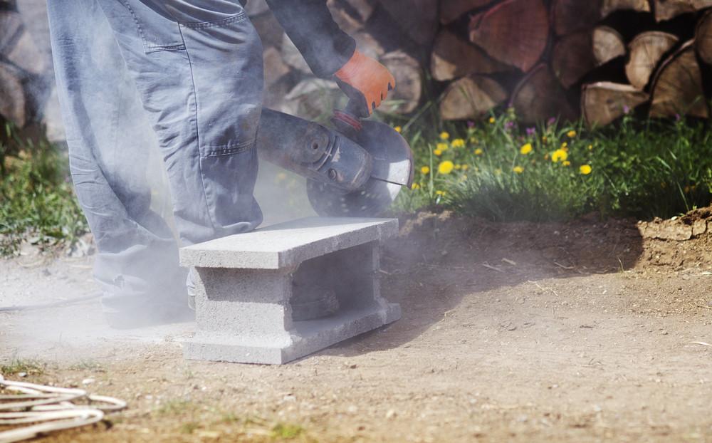 Bricklayer cutting a brick with circular saw