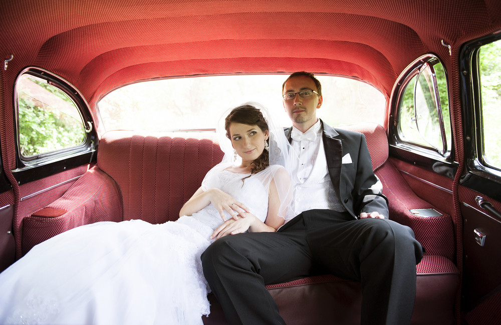 Bride and groom are sitting inside the retro car
