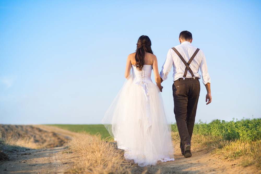 Bride and groom walk in summer nature