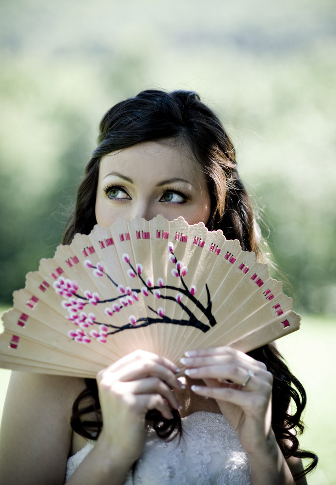 Bride in white wedding dress and summer fan posing at the meadow