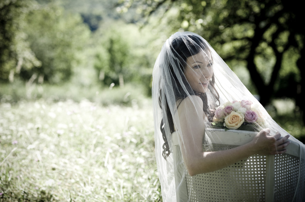 Bride in white wedding dress sitting on chair at the meadow