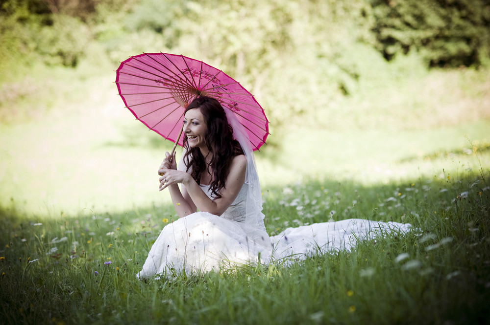 Bride in white wedding dress with umbrella posing at the meadow