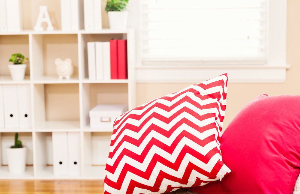 Bright living room interior with red sofa pillows