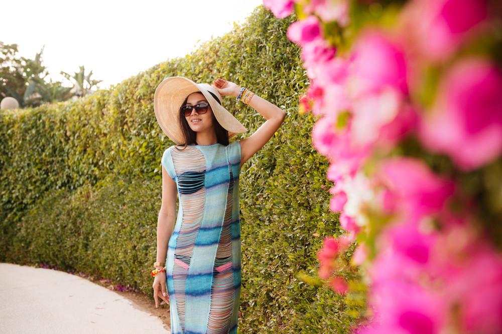 Brunette Woman in beachwear which posing near the flower bush