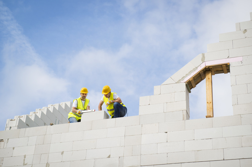 Builders are working on the top of house construction.