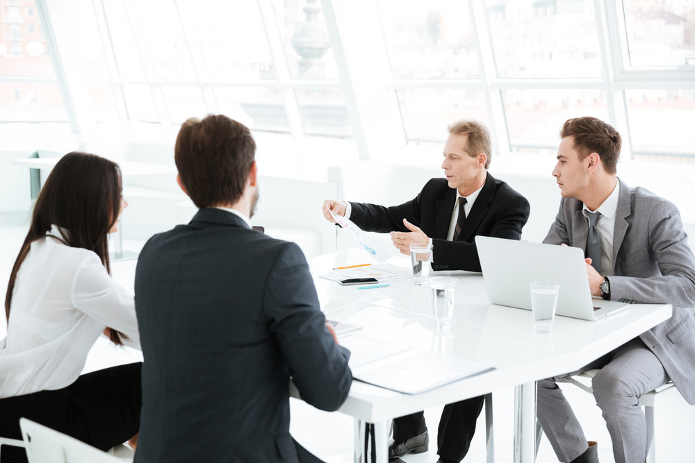 Business group sitting by the table in conference room with laptops