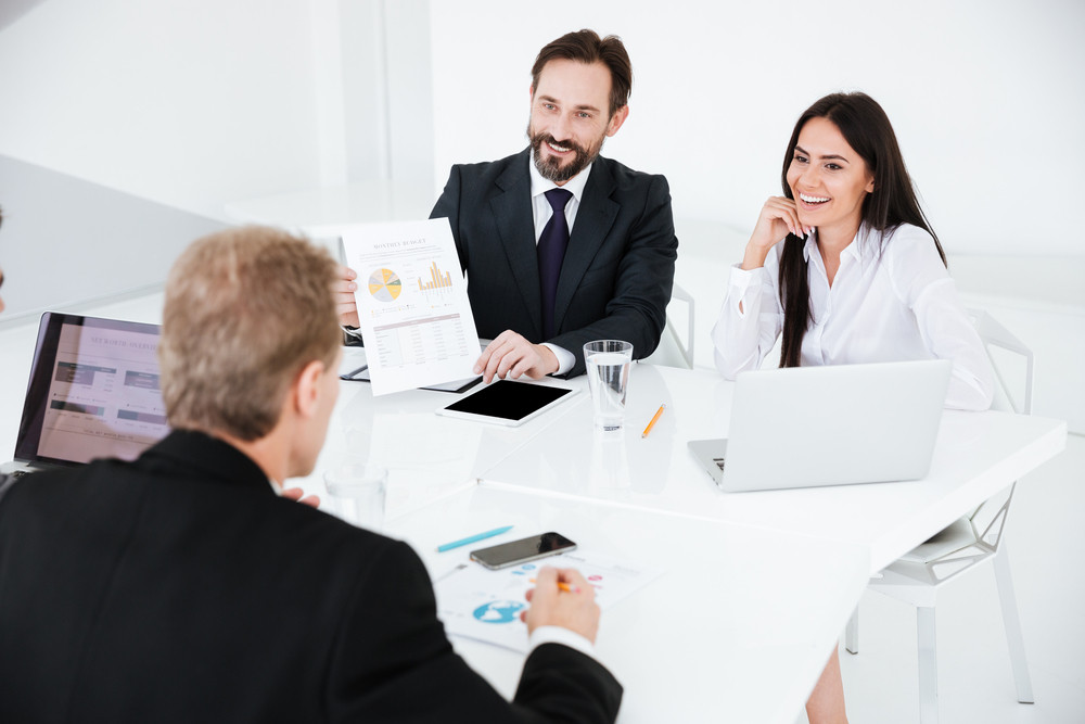Business group sitting by the table in conference room
