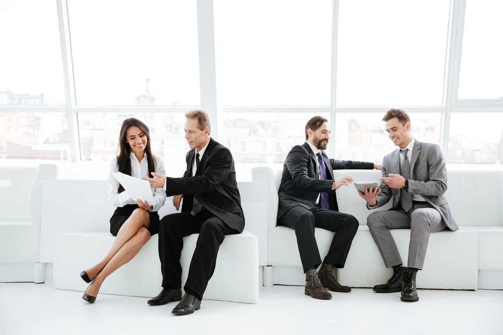 Business group sitting in office on sofa near the window. full length