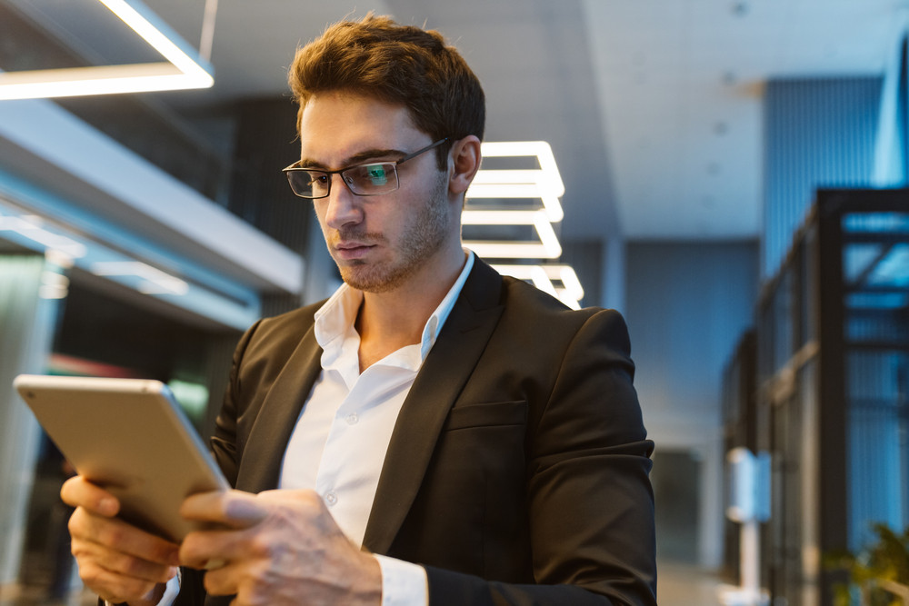 Business man in glasses and suit holding laptop computer in office