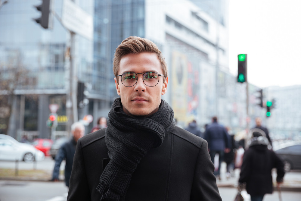 Business man in glasses and warm clothes standing on the street and looking at camera