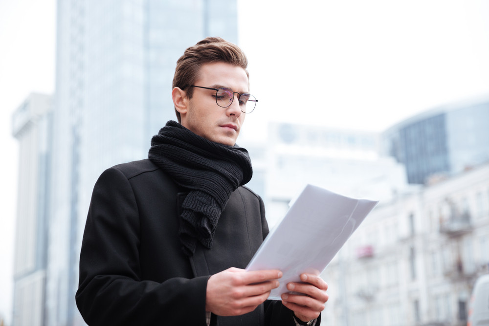 Business man in glasses with documents on the street. looking at documents