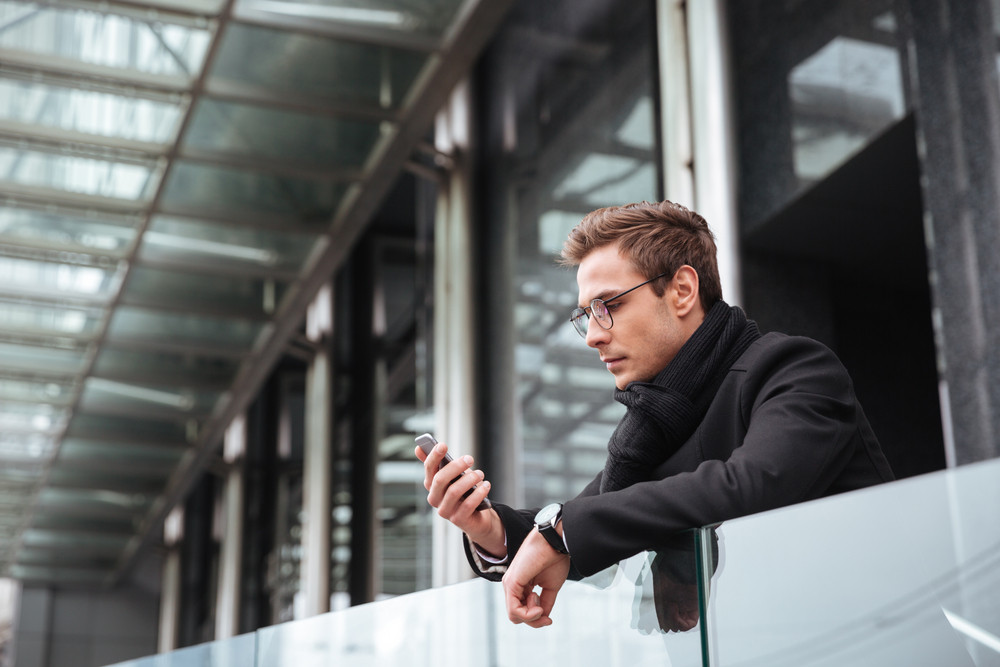 Business man in glasses with phone near the office. side view