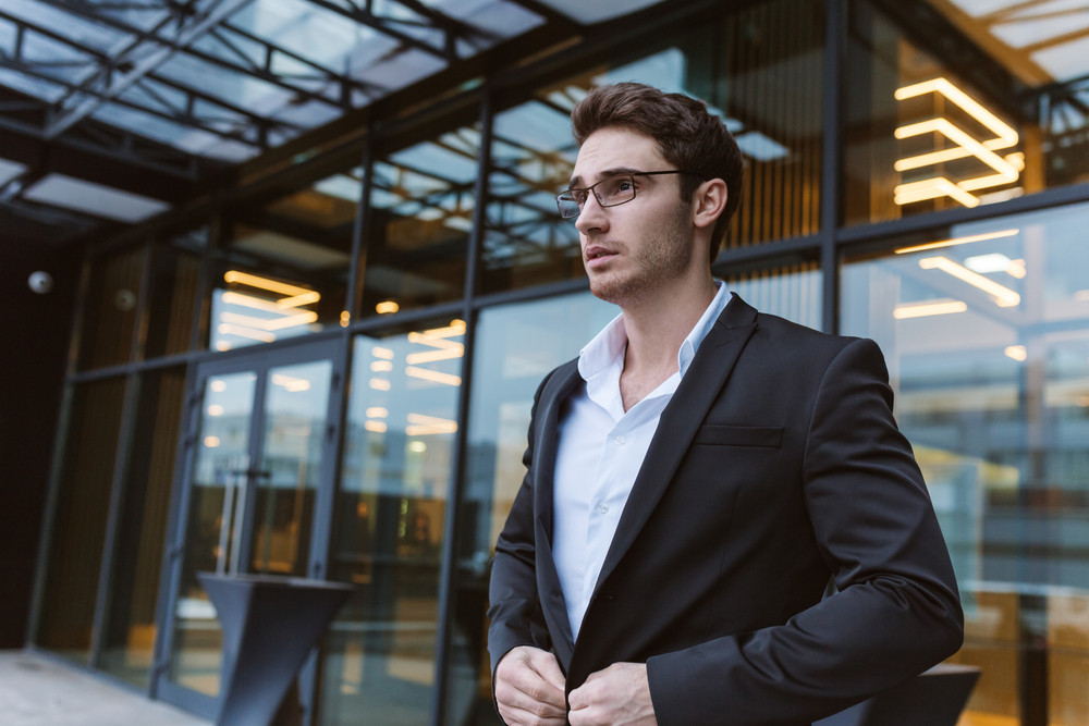 Business man in suit and glasses standing near the office. Side view