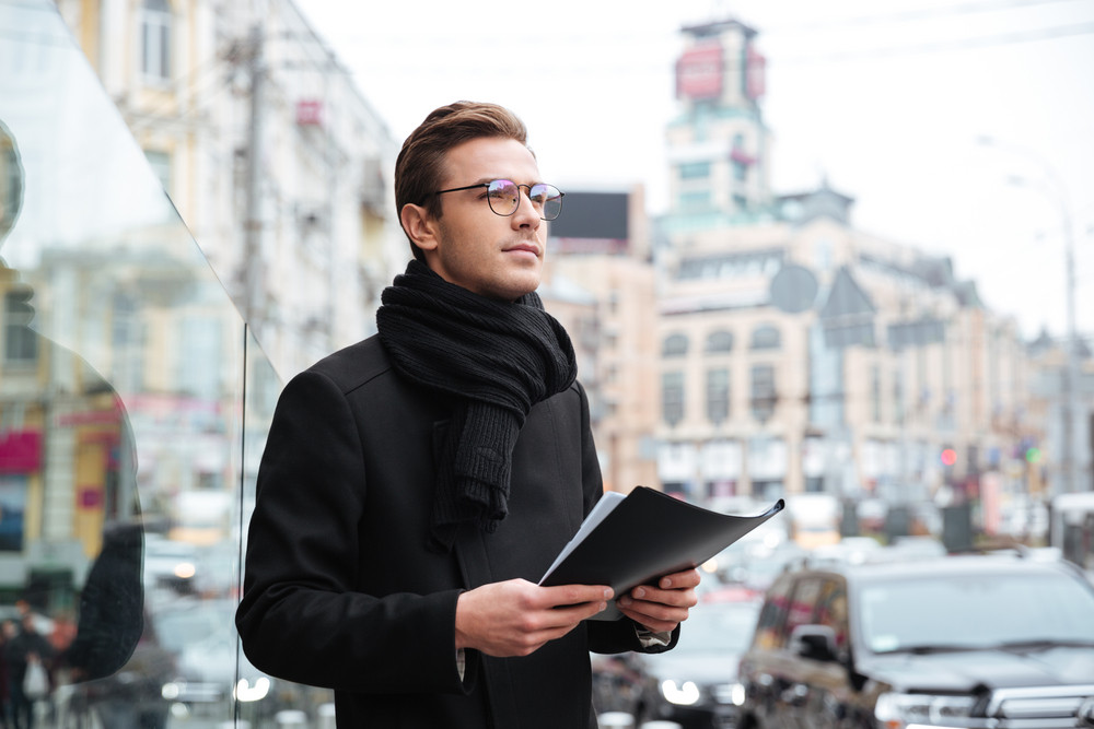 Business man in warm clothes with folder. side view.