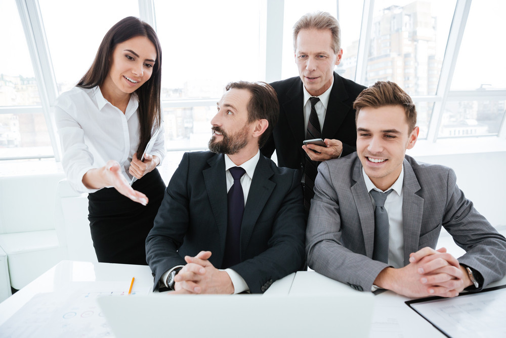 Business people sitting by the table and look at laptop computer in office