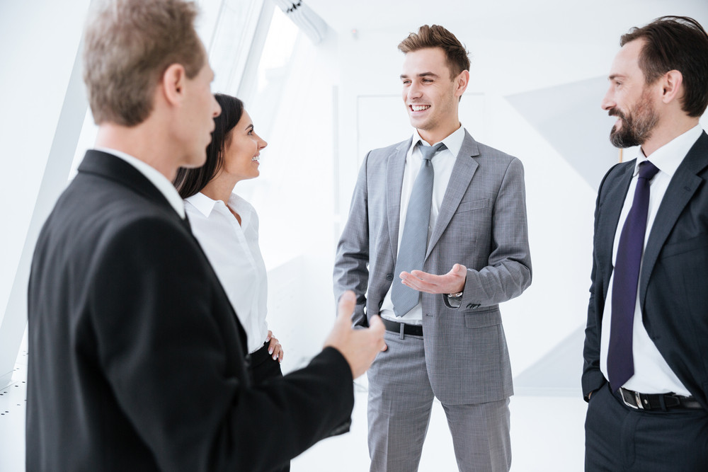 Business people talk near the window in conference room