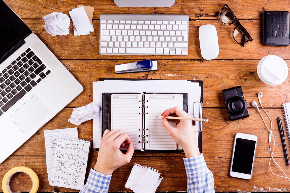 Business person at office desk writing and working. Smart phone, camera, notepad and eyeglasses and various office supplies around the workplace. Flat lay.