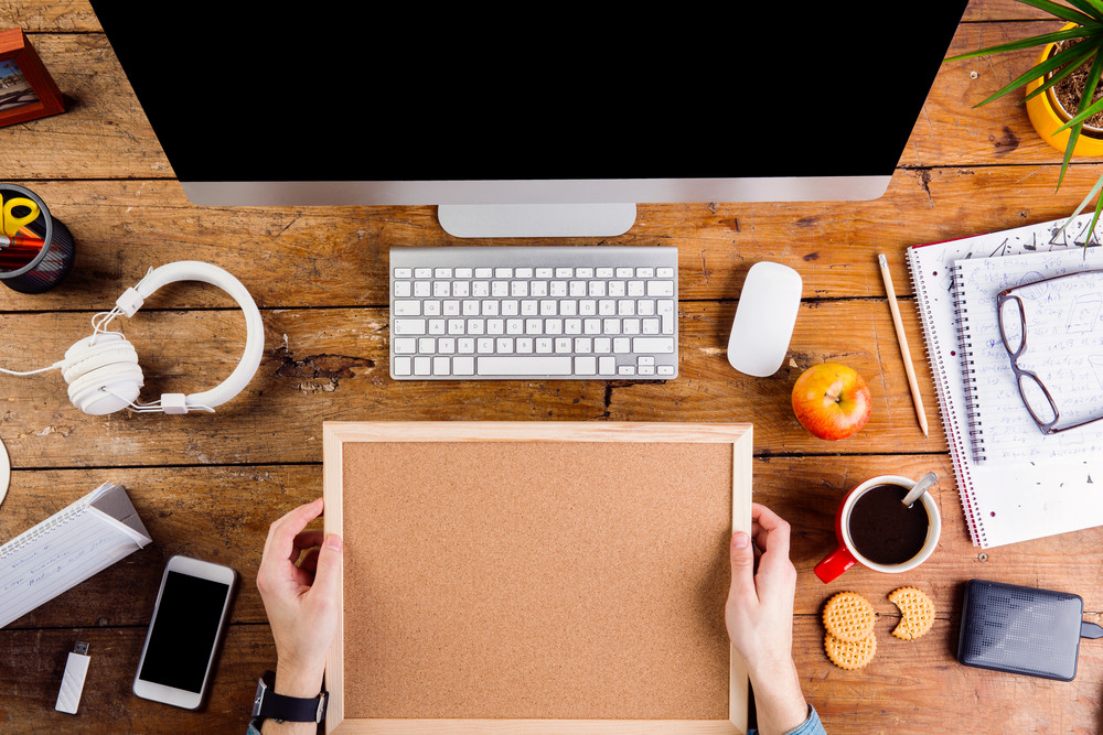 Business person working at office desk. Holding picture frame. Smart watch on hand and smart phone on the table. Copy space. Flat lay.