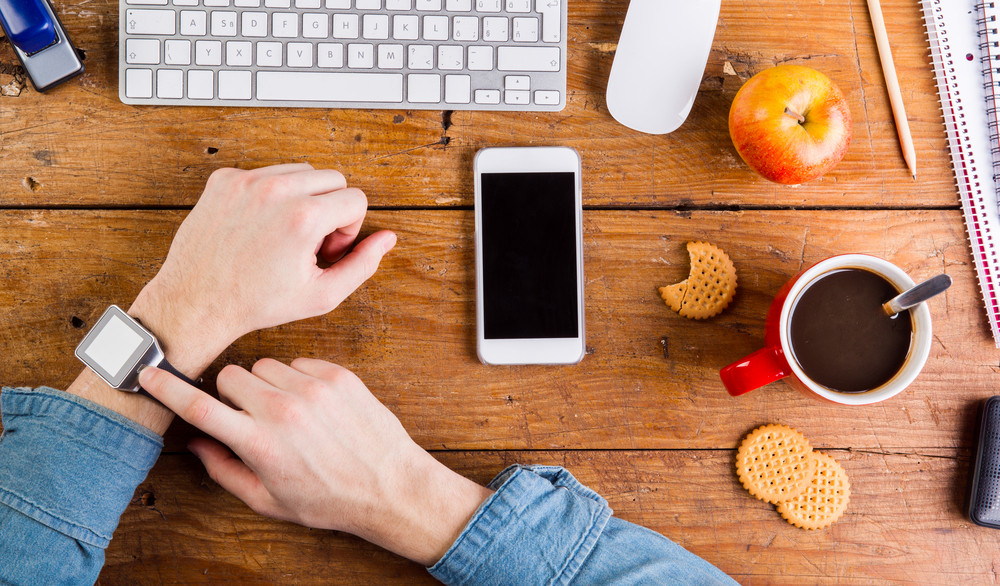 Business person working at office desk. Smart watch on hand and smart phone on the table. Coffee cup, apple and various office supplies around the workplace. Flat lay.