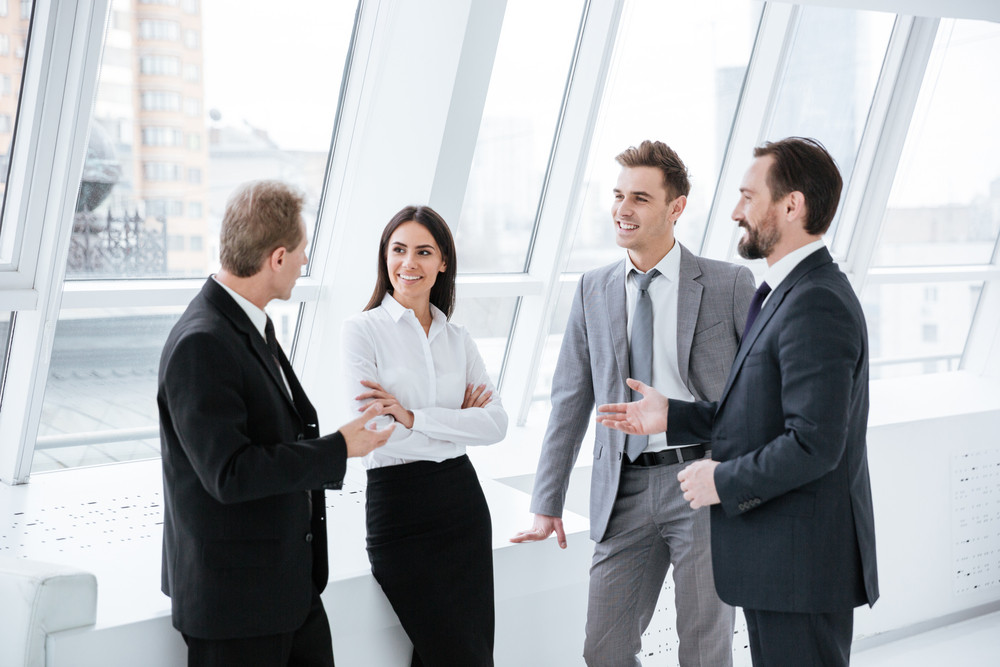 Business team stand and speak near the window in conference room