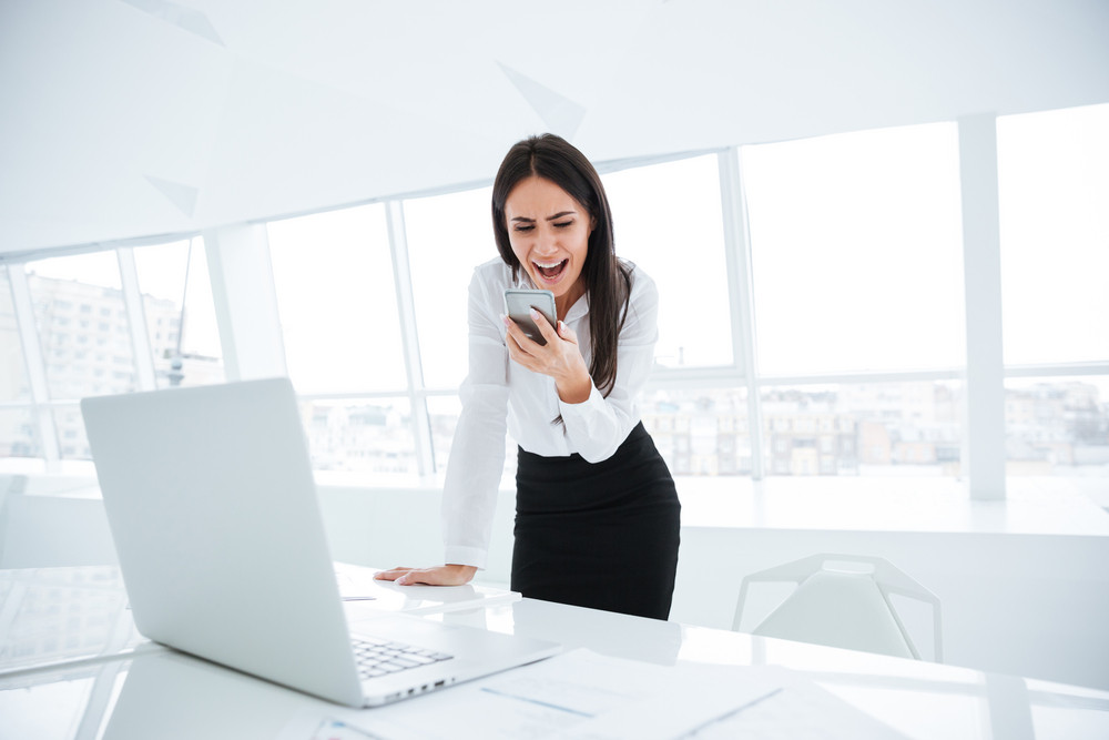 Business woman standing near the table with laptop and screaming at phone in office