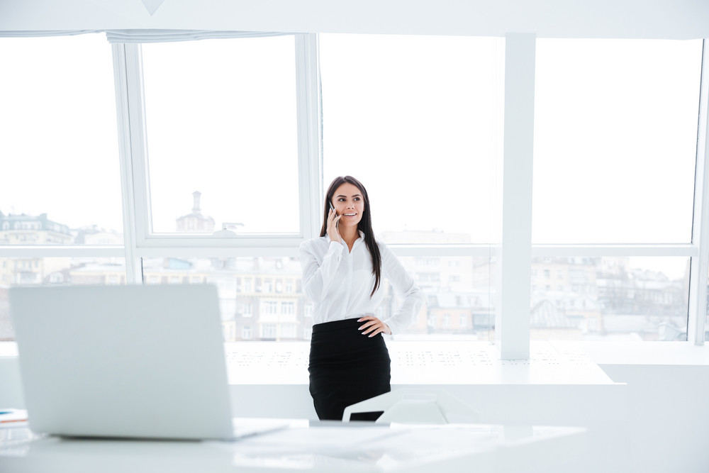 Business woman standing near the window and talking at phone in office
